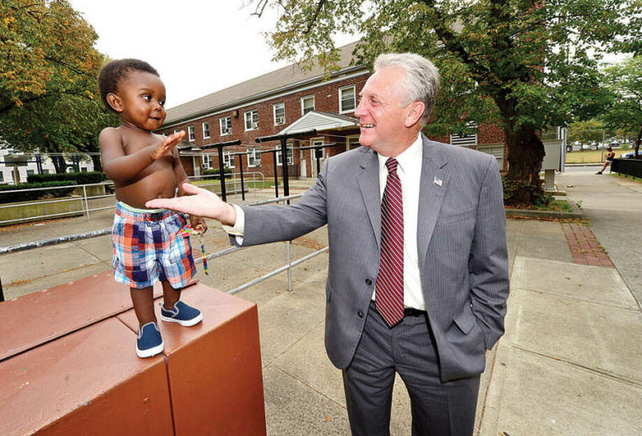 Harry Rilling greets 1 year old Jamaal Holley as he tours Norwalk thanking the community Thursday following his democratic primary win in his candidacy for mayor. Hour photo / Erik Trautmann