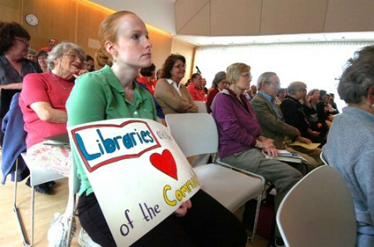 Photo/Alex von Kleydorff. Andrea Faulkner holds a sign as she sits in the audience during a Wilton Library informational question and answer meeting with Speaker of the House Chris Donovan, Wilton Library Director Kathy Leeds and State Rep Peggy Reeves D-143, to discuss proposed state budget cuts affecting libraries.