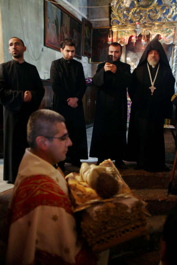 Armenian priests look at a clergyman carrying baby Jesus, during midnight Christmas mass at the Church of Nativity, traditionally believed by Christians to be the birthplace of Jesus Christ, in the West Bank town of Bethlehem on Christmas Eve, Wednesday, Dec. 25, 2013. (AP Photo/Musa Al-Shaer, Pool)