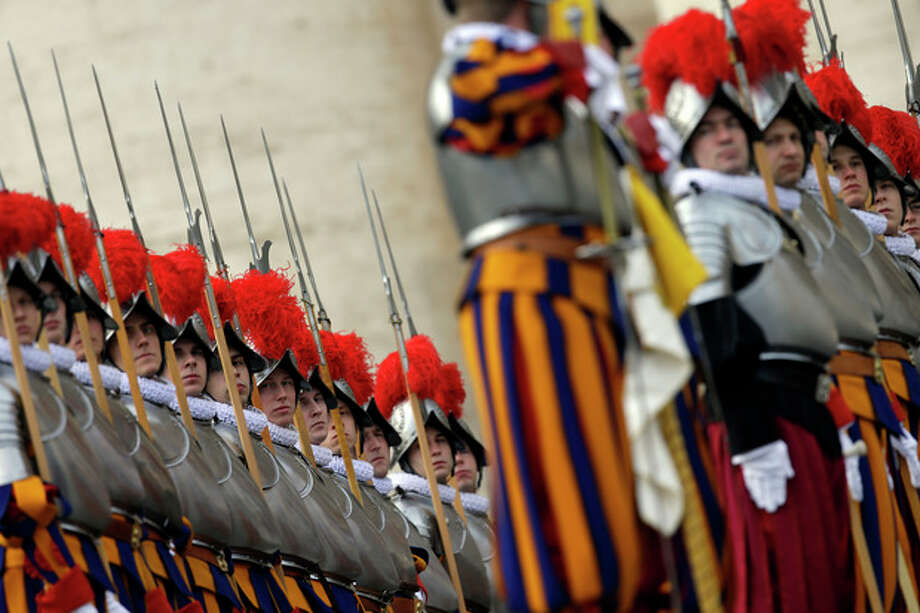 """Swiss guards stand at attention prior to the start of Pope Francis """"Urbi et Orbi"""" (to the City and to the World) message he delivered from the central balcony of St. Peter's Basilica at the Vatican, Wednesday, Dec. 25, 2013. Pope Francis on Christmas day is wishing for a better world, with peace for the land of Jesus' birth, for Syria and Africa as well as for the dignity of migrants and refugees fleeing misery and conflict. Francis spoke from the central balcony of St. Peter's Basilica Wednesday to tens of thousands of tourists, pilgrims and Romans in the square below. He said he was joining in the song of Christmas angels with all those hoping """"for a better world,"""" and with those who """"care for others, humbly."""" (AP Photo/Gregorio Borgia) / AP"""