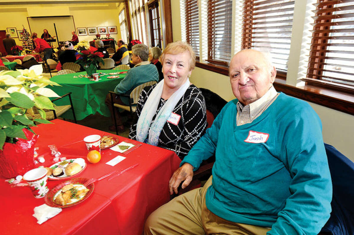 Hour photo / Erik Trautmann Maria and Josepg Dragonetti attend the Saugatuck Congregational Church and Temple Israel Christmas Day Community Open House on Wednesday at the Westport Senior Center.