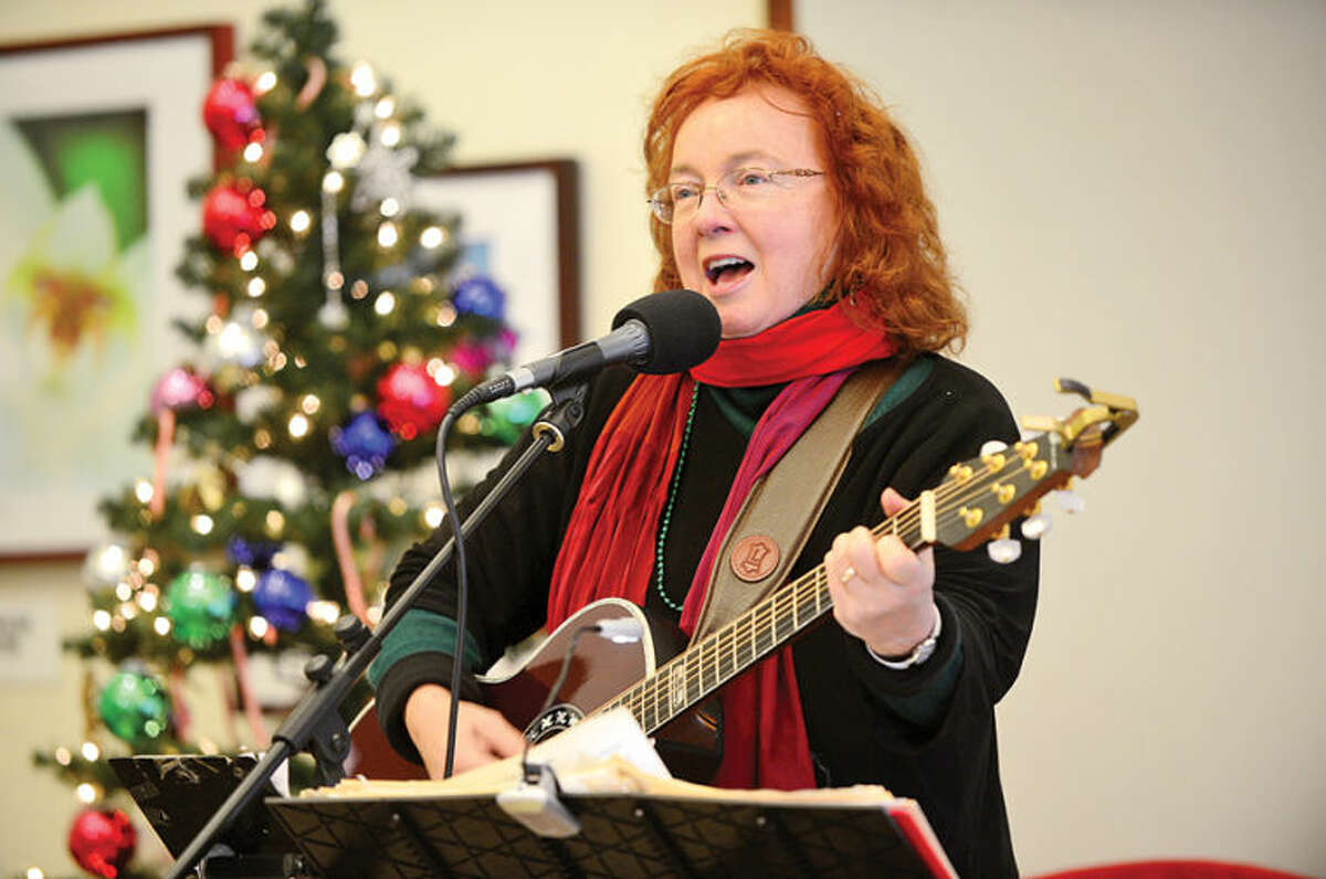 Hour photo / Erik Trautmann Suzanne Sheridan sings Christmas songs during the Saugatuck Congregational Church and Temple Israel Christmas Day Community Open House on Wednesday at the Westport Senior Center.
