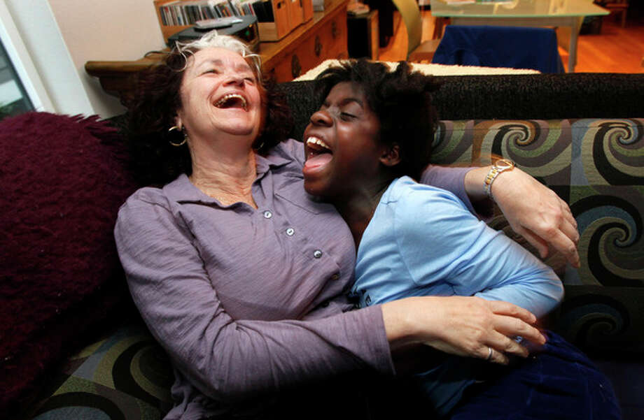 FILE - In this Tuesday, Jan. 18, 2011 file photo, Laura Brenner, left, laughs with her adopted daughter Ketia Brenner, 9, on the couch of their living room in Seattle. Ketia was rescued and adopted in the wake of the massive January 2010 earthquake in Haiti. (AP Photo/Elaine Thompson) / AP