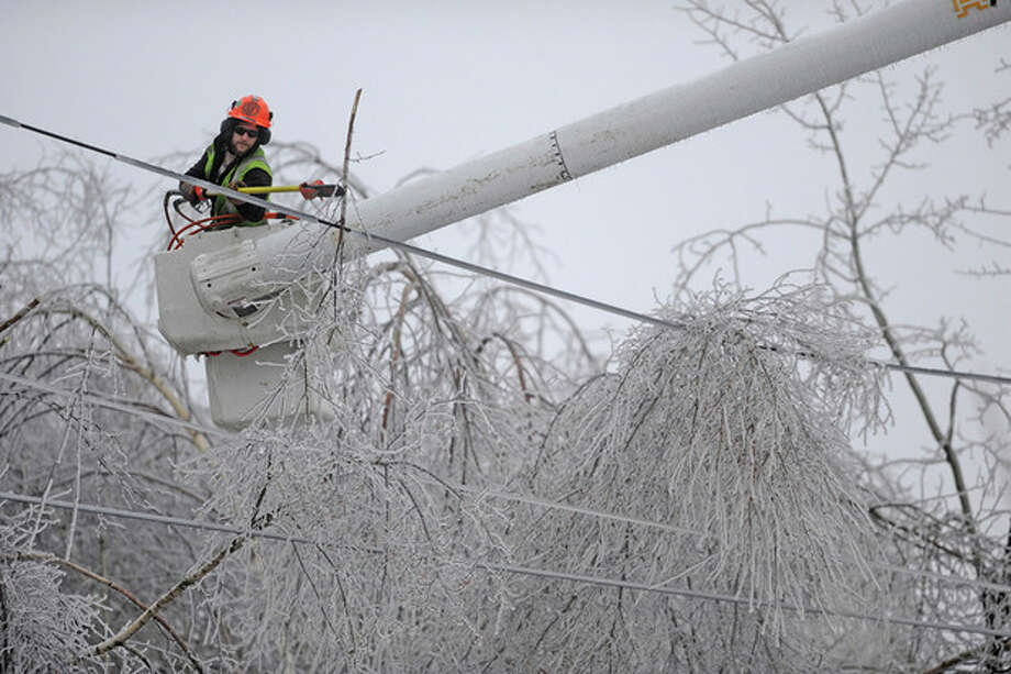 Andrew Powers, an arborist with Asplundh Tree Experts, clears iced branches from power lines along Mayflower Heights Drive in Waterville, Maine, on Monday, Dec. 23, 2013. Central Maine Power said nearly 57,000 were without power Monday afternoon, up from 29,000 it had been reporting earlier. Hardest hit was Kennebec County with about 20,000 and Waldo County at nearly 15,000 customers without power. (AP Photo/Morning Sentinel, Michael G. Seamans) / The Central Maine Morning Sentinel