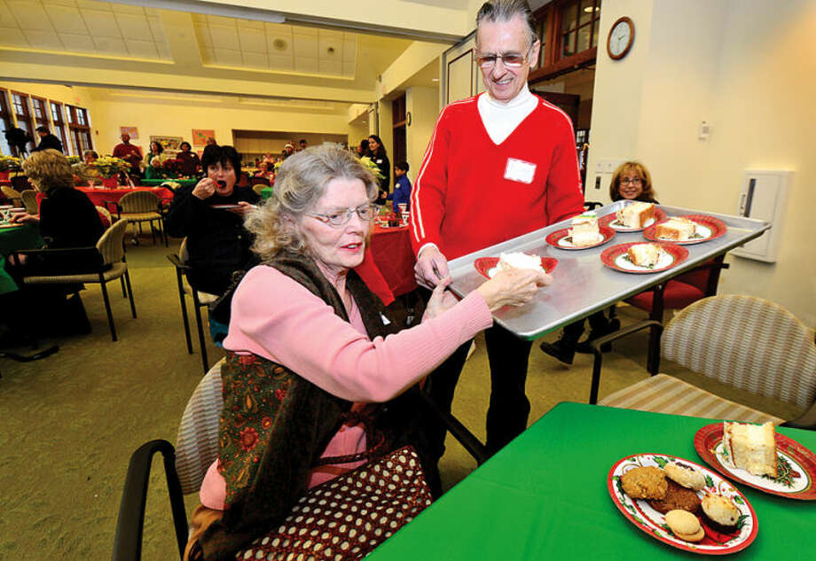 Hour photo / Erik Trautmann Volunteer Maury Hatfirld serves up cake to Barbara Duffy during the Saugatuck Congregational Church and Temple Israel Christmas Day Community Open House on Wednesday at the Westport Senior Center.