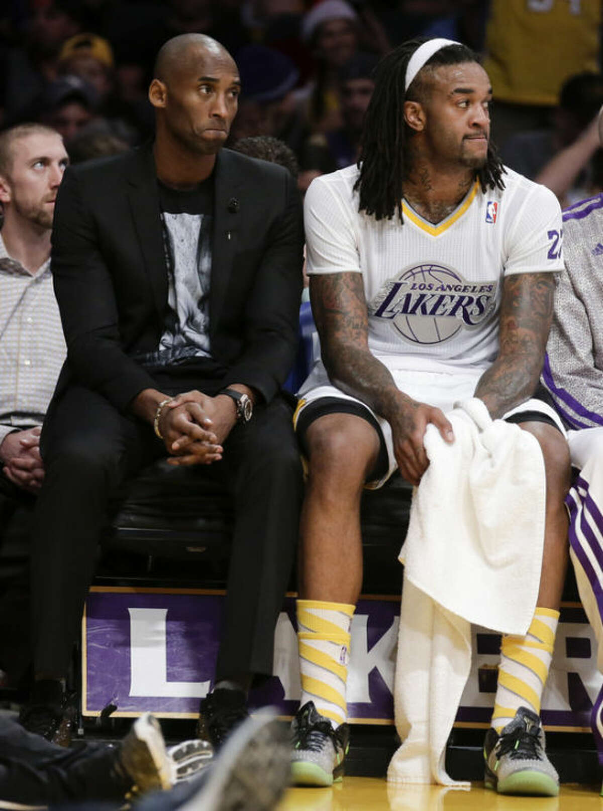 Los Angeles Lakers guard Kobe Bryant, left, and Jordan Hill sift on the bench during the first half of the Lakers' NBA basketball game against the Miami Heat in Los Angeles, Wednesday, Dec. 25, 2013. (AP Photo/Chris Carlson)