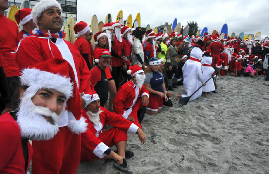 "In this Tuesday, Dec. 24, 2013 photo, Shaylona Kirk, of Cocoa Beach, left, peeks at the camera during the photo shoot of over 210 surfers dressed as Santa Claus, elves and snowmen at the fourth annual ""surfing Santas"" event in Cocoa Beach, Fla. Organizer George Trosset said he may move the holiday event to downtown Cocoa Beach next year to accommodate growing crowds. He started the tradition in 2009 with a few family members after seeing a television commercial featuring people surfing in Santa Claus attire. (AP Photo/Florida Today, Malcolm Denemark) NO SALES"