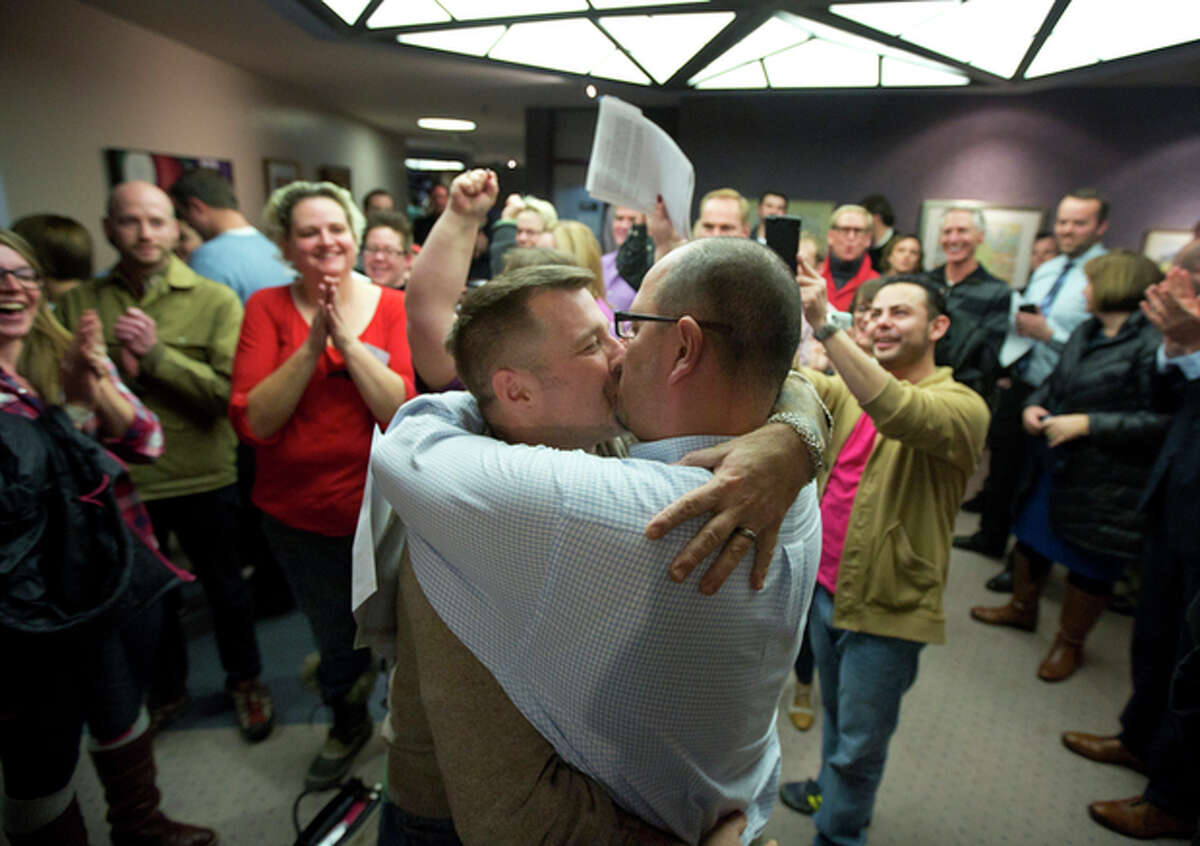 FILE - In this Friday, Dec. 20, 2013 file photo, Chris Serrano, left, and Clifton Webb kiss after being married, as people wait in line to get licenses outside of the marriage division of the Salt Lake County Clerk's Office in Salt Lake City. The last six months of 2013 have provided a frenzy of court decisions and laws in favor of gay marriage, punctuated by a ruling in heavily Mormon Utah that has allowed hundreds of same-sex couples to wed in the last week. The U.S. Supreme Court opened the floodgates with its June ruling that overturned a 1996 ban on gay marriage, and the change has been swift. Judges in Utah, New Mexico and Ohio have all ruled in favor of gay marriage in the past week. (AP Photo/Kim Raff, File)