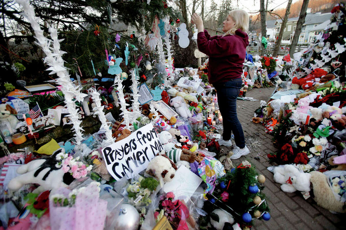 FILE - In this Dec. 20, 2012 file photo, Nancy Hotchkiss of Naugatuck, Conn. hangs an ornament on a tree at a memorial for the Sandy Hook Elementary School shooting victims in Newtown, Conn., where 20 children and six educators died on Dec. 14, 2012. The town decided to keep hundreds of thousands of cards, letters, banners, stuffed animals, children?'s art and other items sent to Newtown, either in its original form, as an archived photo or as recycled material that officials are calling ?