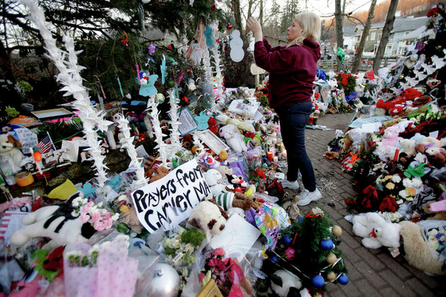 "FILE - In this Dec. 20, 2012 file photo, Nancy Hotchkiss of Naugatuck, Conn. hangs an ornament on a tree at a memorial for the Sandy Hook Elementary School shooting victims in Newtown, Conn., where 20 children and six educators died on Dec. 14, 2012. The town decided to keep hundreds of thousands of cards, letters, banners, stuffed animals, children's art and other items sent to Newtown, either in its original form, as an archived photo or as recycled material that officials are calling ""sacred soil."" Plans call for mixing about 2 cubic yards of the substance into construction materials to perhaps use in the foundation of a new Sandy Hook school or to help construct a permanent memorial to the massacre. (AP Photo/Seth Wenig, File) / AP"
