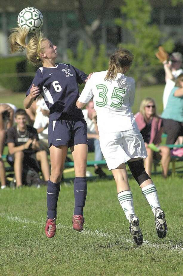 Photo by John Nash OH DEARDORFF Wilton freshman defender Colleen Deardorff goes airborne to battle Trinity Catholic
