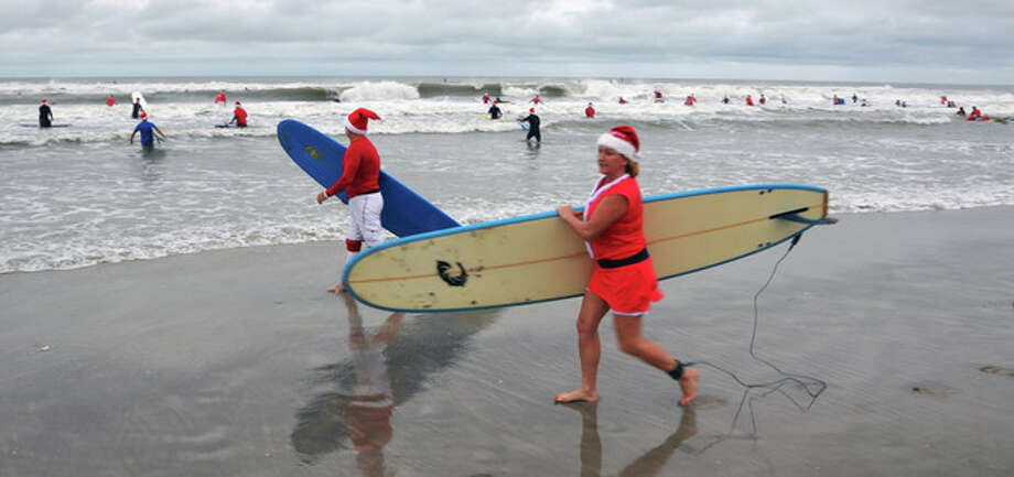 """In this Tuesday, Dec. 24, 2013 photo, Santas head out to the surf during the fourth annual """"surfing Santas"""" event in Cocoa Beach, Fla. Organizer George Trosset said he may move the holiday event to downtown Cocoa Beach next year to accommodate growing crowds. He started the tradition in 2009 with a few family members after seeing a television commercial featuring people surfing in Santa Claus attire. (AP Photo/Florida Today, Malcolm Denemark) NO SALES / Florida Today"""