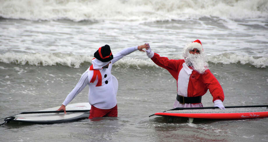 "In this Tuesday, Dec. 24, 2013 photo, George Trosset Jr., dressed as a snowman, left, and his dad, event organizer George Trosset, high five each other out in the waves during the fourth annual ""surfing Santas"" event in Cocoa Beach, Fla. Organizer George Trosset said he may move the holiday event to downtown Cocoa Beach next year to accommodate growing crowds. He started the tradition in 2009 with a few family members after seeing a television commercial featuring people surfing in Santa Claus attire. (AP Photo/Florida Today, Malcolm Denemark) NO SALES / Florida Today"