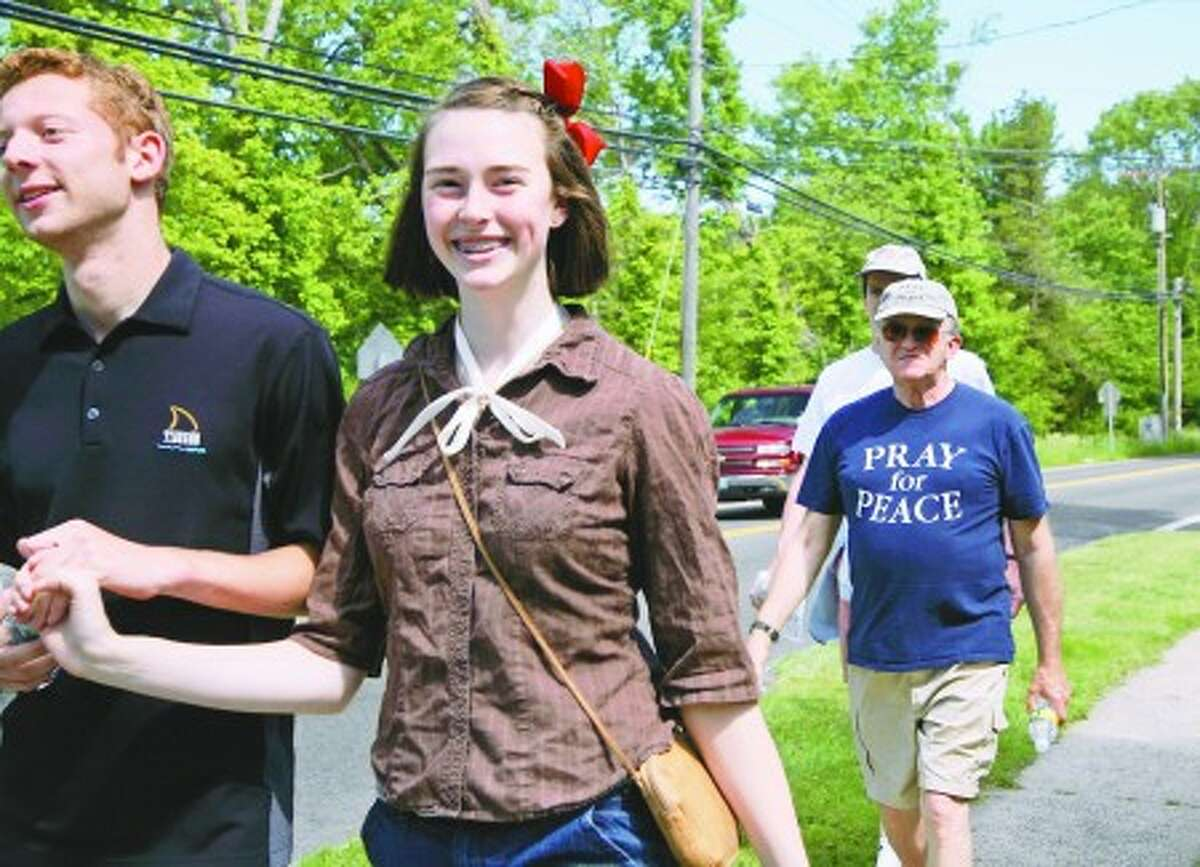 Nick Sykes and Hannah Herde walk in front of Al Forte along side Mansfield Avenue in Darien during the Fairfield County, CT Pray-For-Peace Walk which took place Sunday morning. Hour Photo / Danielle Robinson