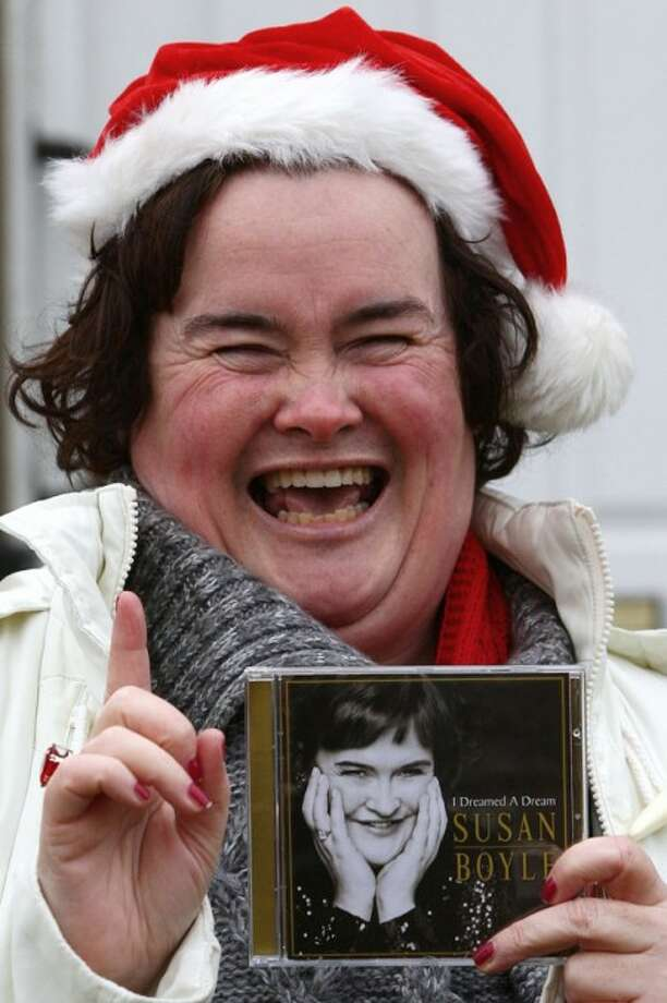 British Singer Susan Boyle gestures as she holds her new album outside her home in Blackburn, Scotland, Tuesday Dec. 1. (AP Photo/PA, Andrew Milligan)