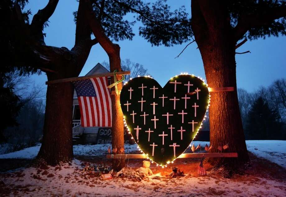 FILE - In this Saturday, Dec. 14, 2013, file photo, a makeshift memorial with crosses for the victims of the Sandy Hook massacre stands outside a home in Newtown, Conn., the one-year anniversary of the shootings. Connecticut authorities said they planned Friday, Dec. 27, 2013, to release state police documents from the investigation into last year's Newtown school massacre. (AP Photo/Robert F. Bukaty, File) / AP