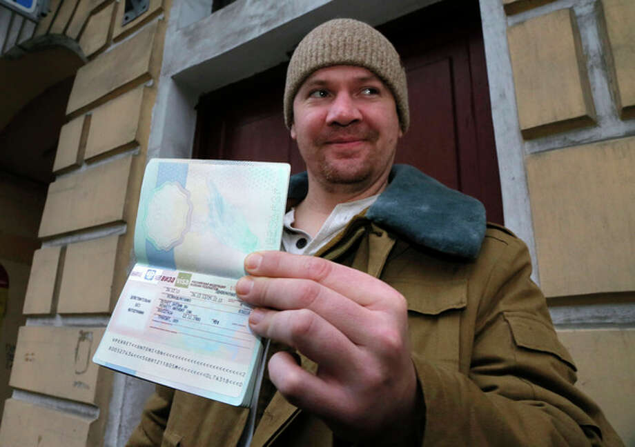 Greenpeace International activist Anthony Perrett of the United Kingdom shows to journalists his passport with permission to leave Russia, near the Federal Migration Service in St. Petersburg, Russia, Thursday, Dec. 26, 2013. Russian investigators have dropped charges against all but one of the 30 crew of a Greenpeace ship, who were accused of hooliganism following a protest outside a Russian oil rig in the Arctic. (AP Photo/Dmitry Lovetsky) / AP