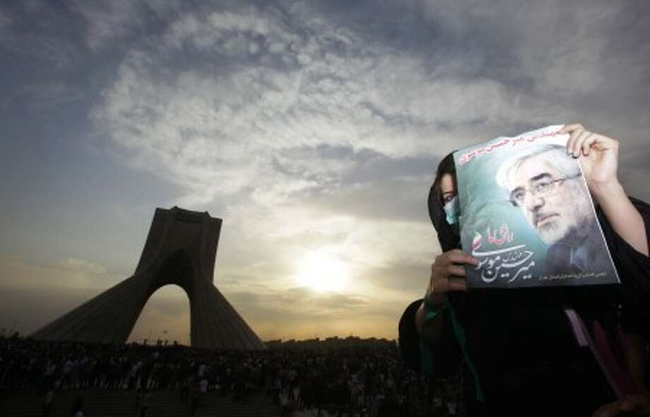 A female demonstrator holds up a poster of leading opposition presidential candidate Mir Hossein Mousavi, who claims there was voting fraud in Friday''s election, as she and hundreds of thousands of others turn out to protest the result of the election at a mass rally in Azadi (Freedom) square in Tehran, Iran, Monday, June 15, 2009. (AP Photo/Ben Curtis)
