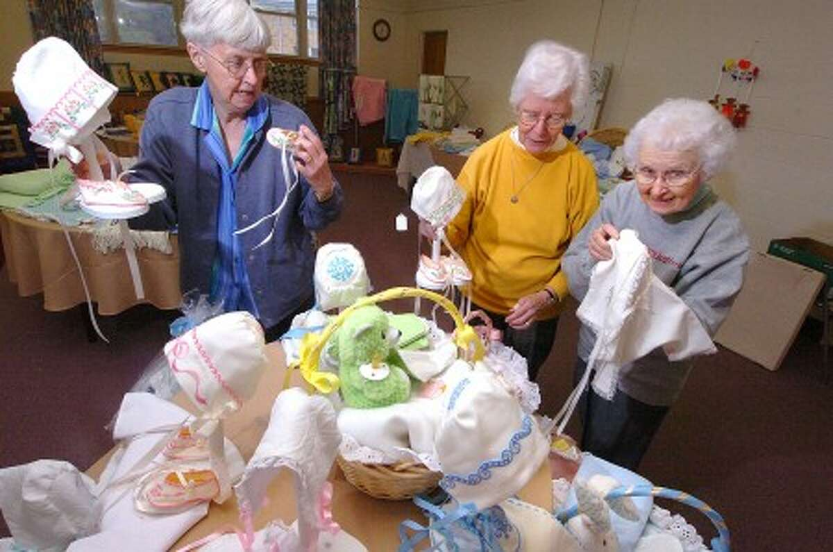Photo/Alex von Kleydorff. l-r Sisters Margaret Van Rossem, Carol Datz and Marie Anna Moltz prepare a table full of baby clothing items embroidered by Sister Marie for the School Sisters of Notre Dame Oktoberfest fair this weekend.