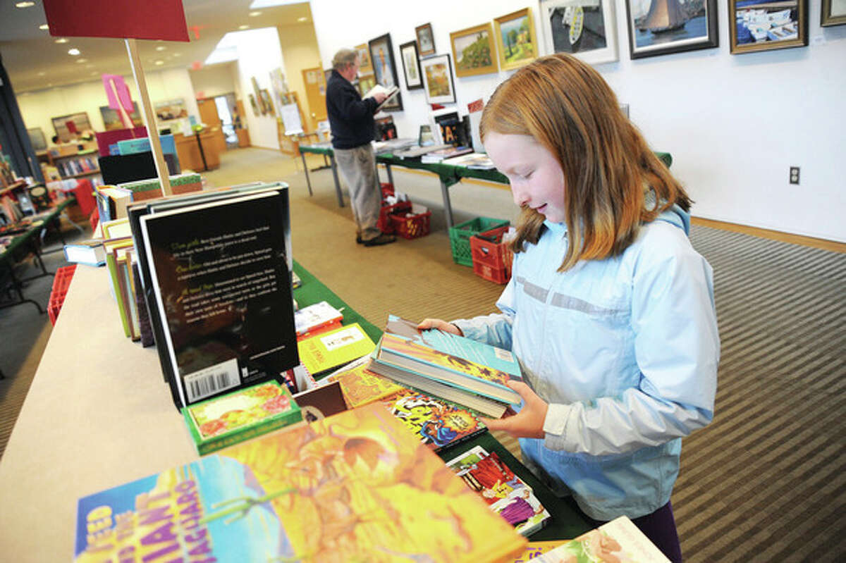 Photo by Matthew Vinci Caroline Mahony, 10, sorts through the children's section during the Wilton Library's Holiday Book Sale on Monday. The book sale, which ended Monday, sold hundreds of bargain books, CDs and DVDs.