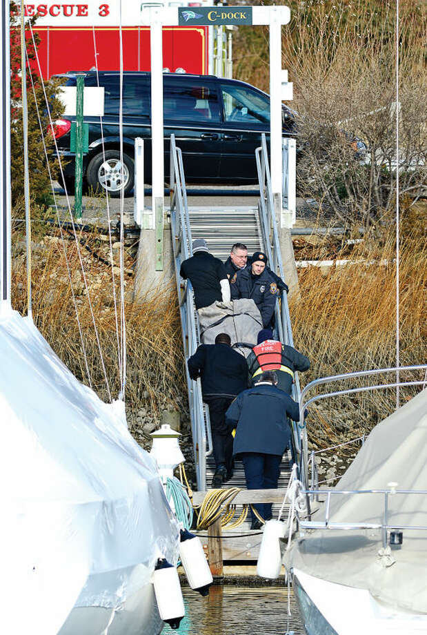 Hour photo / Erik Trautmann Westport police and the state coroner's office remove the lifeless body that was discovered in Saugatuck Harbor Friday morning.