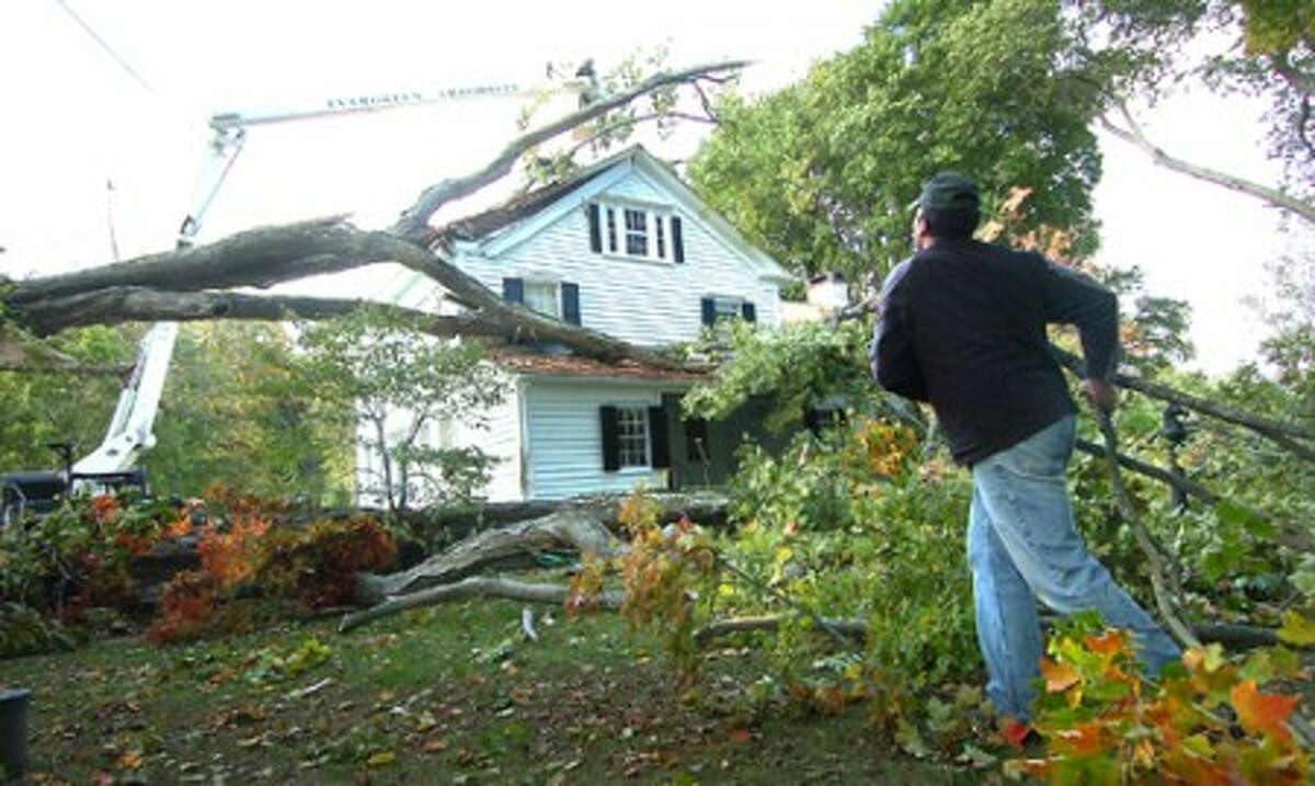 Photo/Alex von Kleydorff. Charlie Hyatt owner of Evergreen Arborists clears some of the cut branches as workers startt to remove a more than 150yr old Sugar Maple from the top of a house on Drum Hill rd in Wilton. Heavy winds in the area are believed to be the cause of the mature tree snapping at around 2pm and landing directly on the roof.