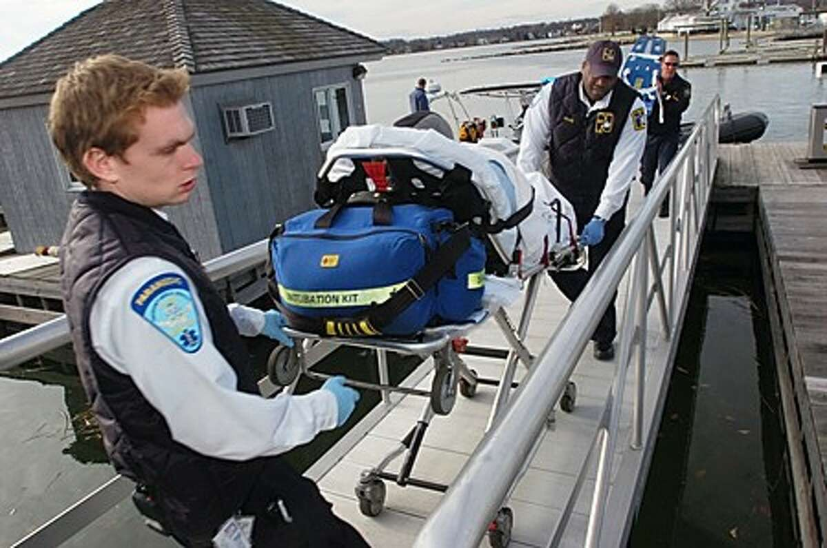 Norwalk paramedics Matt Soicher and Charly Luly transport a 68 year old woman from Cove Marina that had capsized her kayak off the coast of Cockenoe Island and been rescued by passers-by. Hour photo / Erik Trautmann