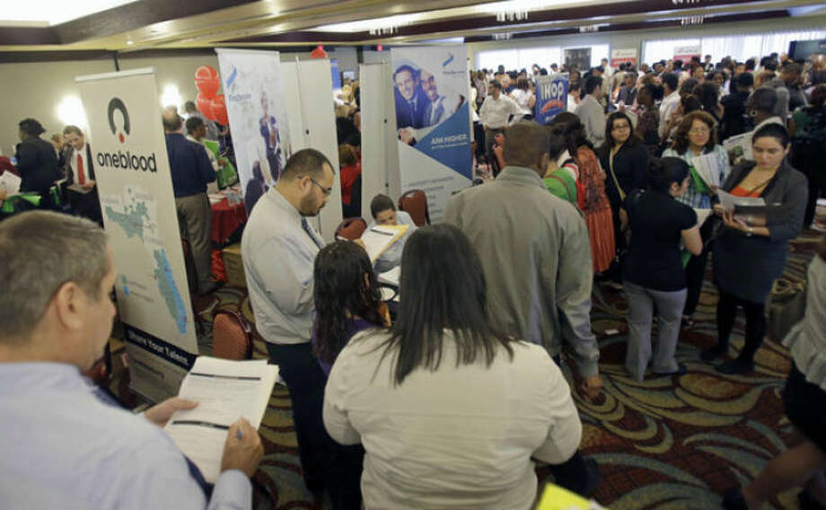FILE - This Aug. 14, 2013 file photo shows job seekers checking out companies at a job fair in Miami Lakes, Fla. More than 1 million Americans are bracing for a harrowing, post-Christmas jolt as federal unemployment benefits come to a sudden halt this weekend. The development entails potentially significant implications for the recovering U.S. economy and sets up a tense battle when Congress reconvenes in the new year. (AP Photo/Alan Diaz, File)