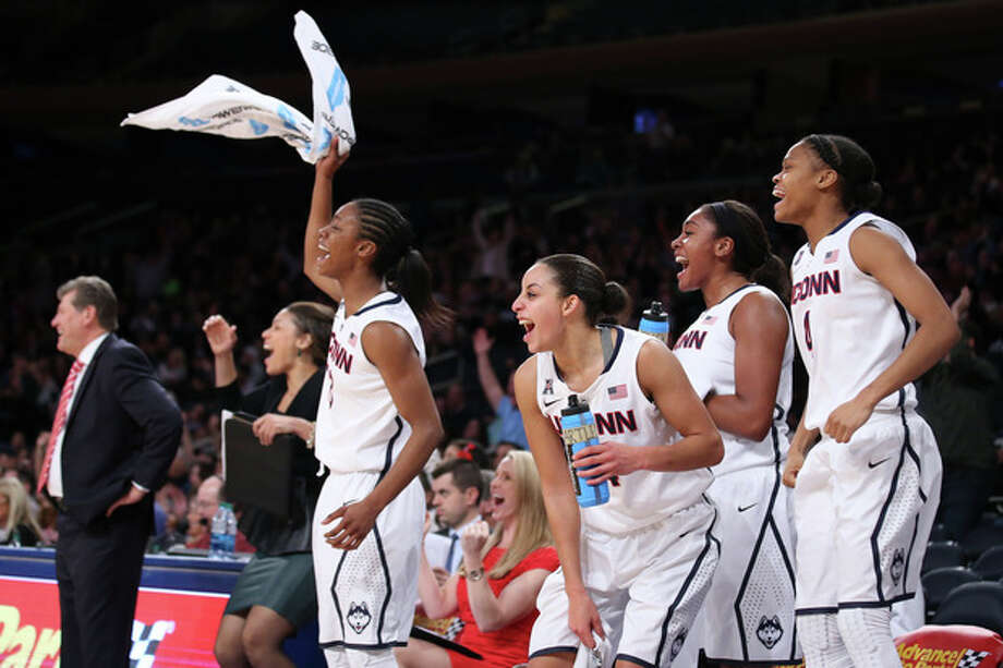 The Connecticut bench celebrates following an NCAA college basketball game against California as part of the Maggie Dixon Basketball Classic at Madison Square Garden, Sunday, Dec. 22, 2013, in New York. Connecticut defeated California 80-47. (AP Photo/John Minchillo) / FR170537 AP