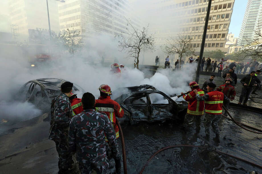 Lebanese firefighters extinguish burned vehicles at the scene of an explosion in Beirut, Lebanon, Friday, Dec. 27, 2013. A powerful bombing rocked a central business district of central Beirut Friday, setting cars ablaze and killing several people, including Mohammed Chatah, a senior aide to former Lebanese Prime Minister Saad Hariri, the National News Agency said. (AP Photo/Bilal Hussein) / AP