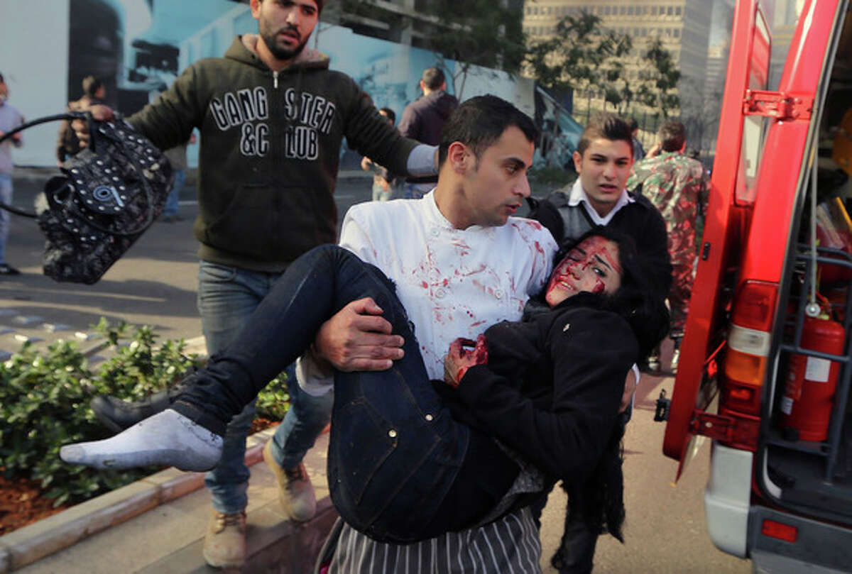 A Lebanese man carries an injured woman at the scene of an explosion in Beirut, Lebanon, Friday, Dec. 27, 2013. A strong explosion has shaken the Lebanese capital, sending black smoke billowing from the center of Beirut. The blast went off a few hundred meters (yards) from the government headquarters and parliament building. (AP Photo/Bilal Hussein)