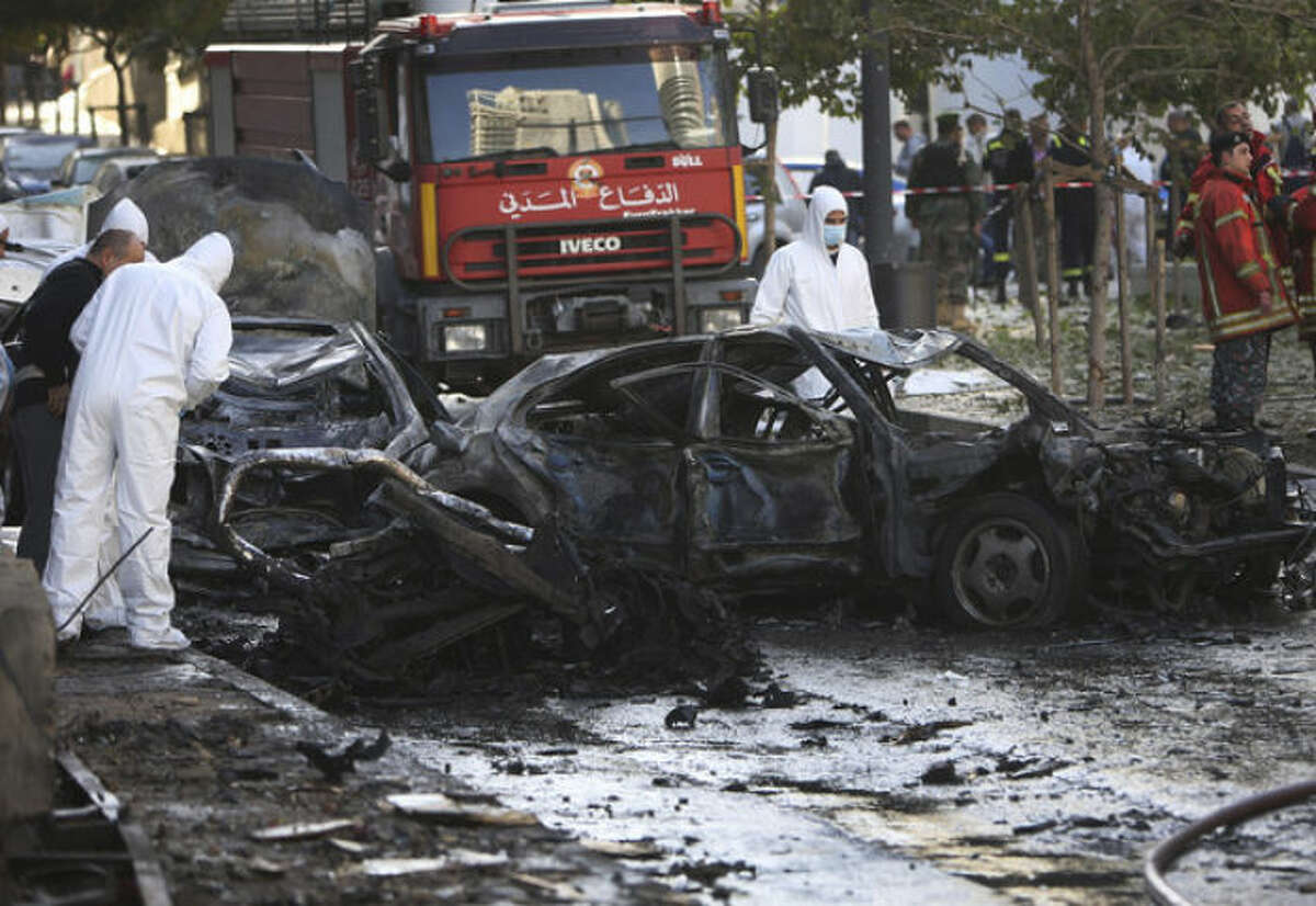 Lebanese army investigators in white coverall inspect at the scene of an explosion in central Beirut, Lebanon, Friday, Dec. 27, 2013. The state news agency said a bombing in central Beirut has killed several people, including a senior aide to former Lebanese Prime Minister Saad Hariri. (AP Photo/Hussein Malla)