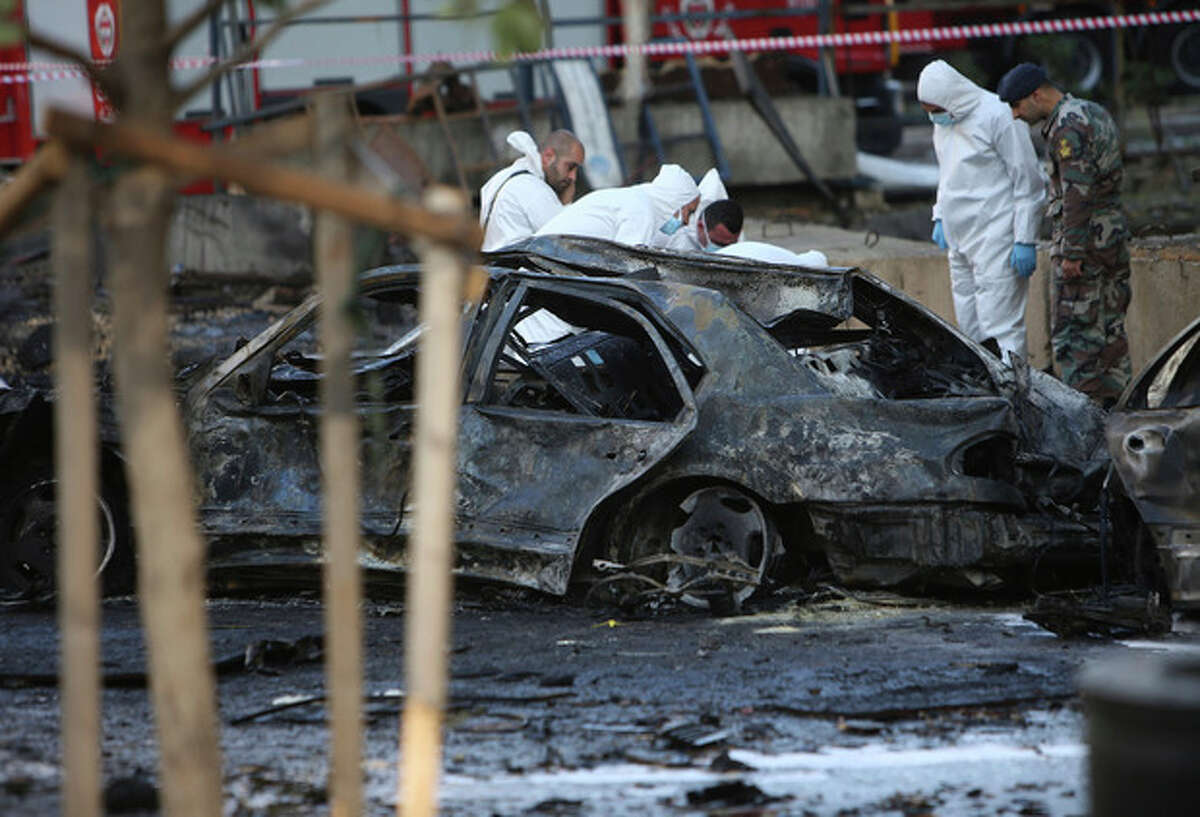 Lebanese army investigators in white coveralls inspect the scene of an explosion in central Beirut, Lebanon, Friday, Dec. 27, 2013. The state news agency said a bombing in central Beirut killed several people, including Mohammed Chatah, a senior aide to former Lebanese Prime Minister Saad Hariri. (AP Photo/Hussein Malla)