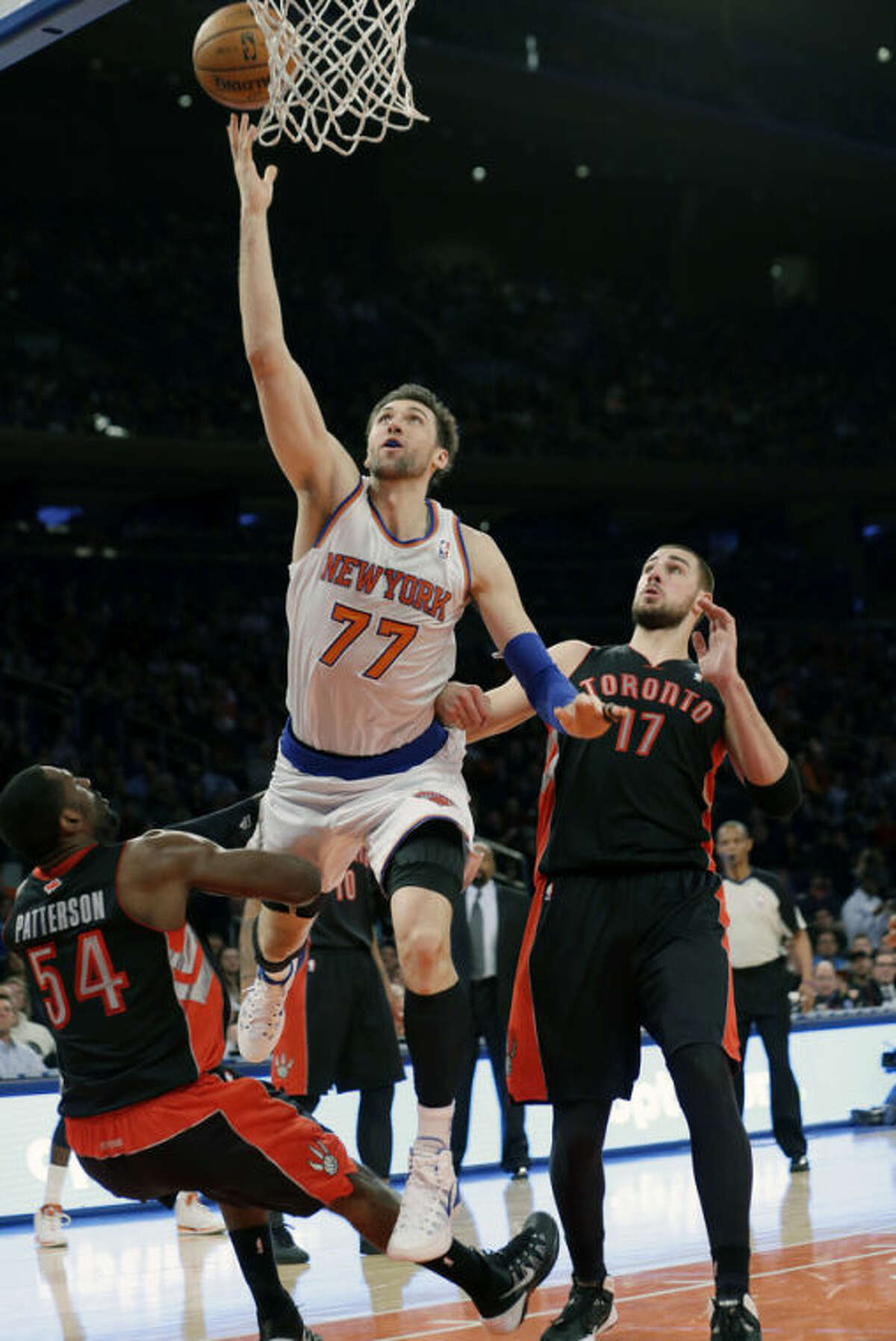 New York Knicks' Andrea Bargnani (77), of Italy, shoots over Toronto Raptors' Patrick Patterson (54) as Jonas Valanciunas (17), of Lithuania, stands near during the first half of an NBA basketball game Friday, Dec. 27, 2013, in New York. (AP Photo/Frank Franklin II)