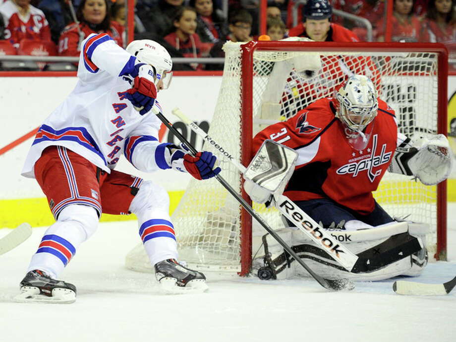 New York Rangers center Dominic Moore, left, tries to get the puck past Washington Capitals goalie Philipp Grubauer (31) during the second period an NHL hockey game, Friday, Dec. 27, 2013, in Washington. (AP Photo/Nick Wass) / FR67404 AP