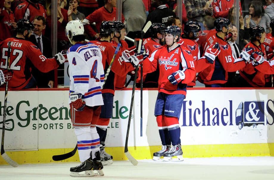 Washington Capitals center Nicklas Backstrom (19), of Sweden, celebrates his goal with teammates as New York Rangers defenseman Michael Del Zotto (4) skates by during the second period an NHL hockey game, Friday, Dec. 27, 2013, in Washington. (AP Photo/Nick Wass) / FR67404 AP