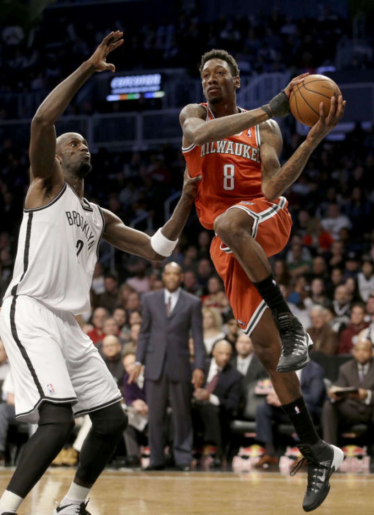 Milwaukee Bucks' Larry Sanders, right, passes around Brooklyn Nets' Kevin Garnett during the first half of an NBA basketball game at the Barclays Center, Friday, Dec. 27, 2013, in New York. (AP Photo/Seth Wenig)