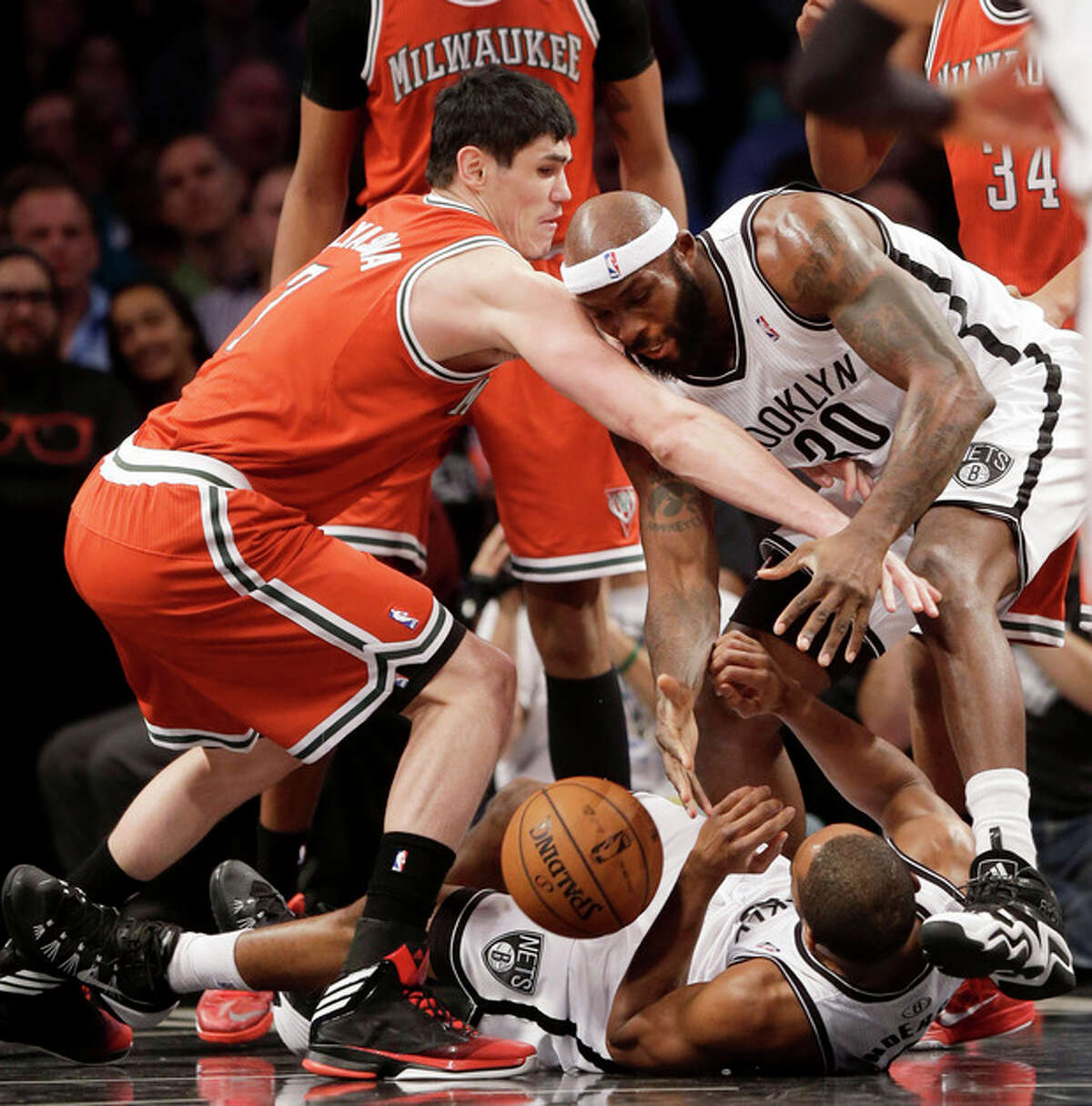 Milwaukee Bucks' Ersan Ilyasova, left, fights for a rebound with Brooklyn Nets' Reggie Evans, right, and Alan Anderson, bottom, during the first half of an NBA basketball game at the Barclays Center, Friday, Dec. 27, 2013, in New York. (AP Photo/Seth Wenig)