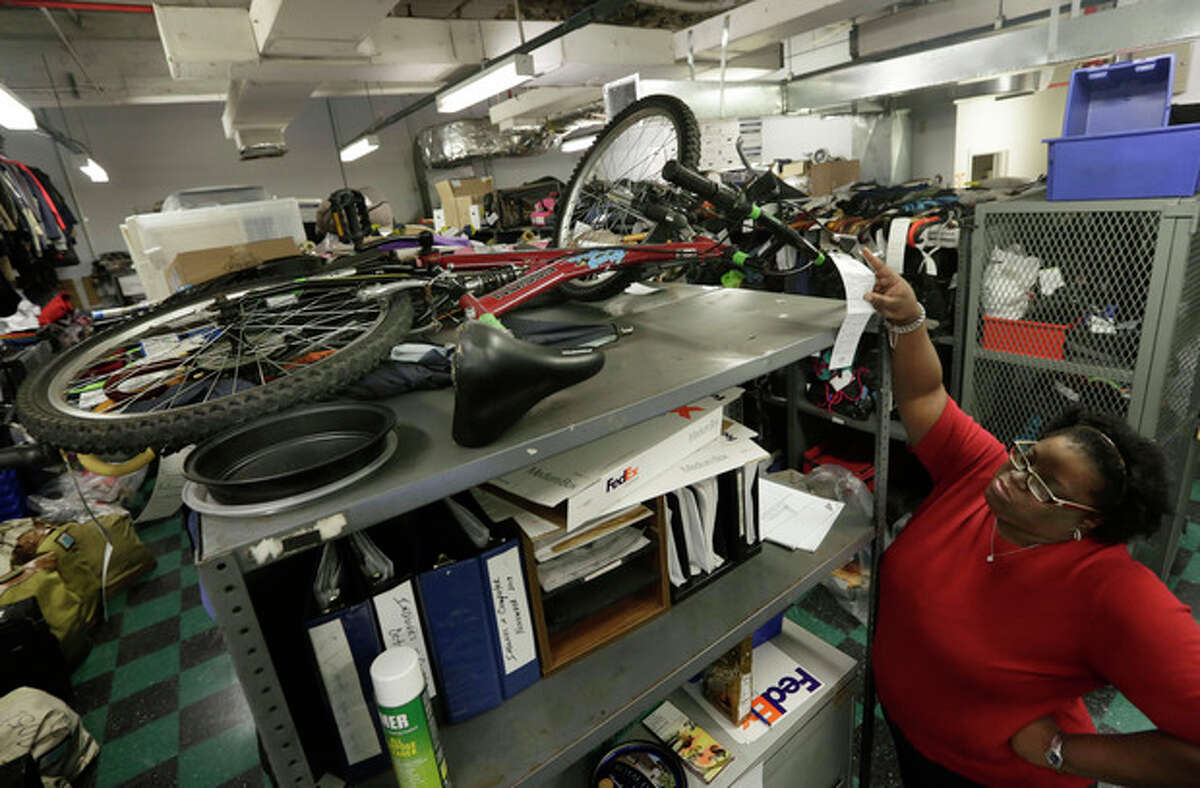 In this Tuesday, Dec. 17, 2013 photo, manager Melissa Gissentanner looks at the tag of a lost bicycle in the MTA Metro-North Lost and Found department, at New York's Grand Central Terminal. Gissentanner said the MTA takes pride in getting items back to their owners, boasting a 60 percent return rate. ?