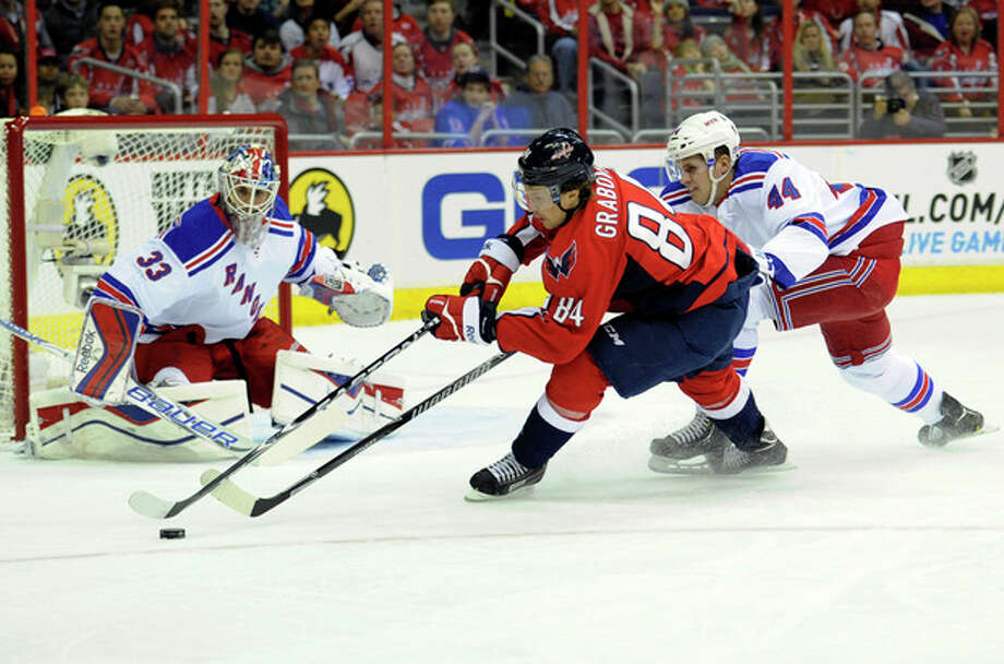 New York Rangers defenseman Justin Falk (44) battles for the puck against Washington Capitals center Mikhail Grabovski (84), of Germany, during the first period an NHL hockey game, Friday, Dec. 27, 2013, in Washington. Also seen is Rangers goalie Cam Talbot (33). (AP Photo/Nick Wass) / FR67404 AP