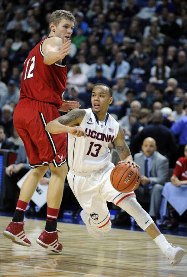 Connecticut's Shabazz Napier (13) drives past Eastern Washington's Martin Seiferth (12) during the firsta half of an NCAA college basketball game in Bridgeport, Conn., Saturday, Dec. 28, 2013. (AP Photo/Fred Beckham)