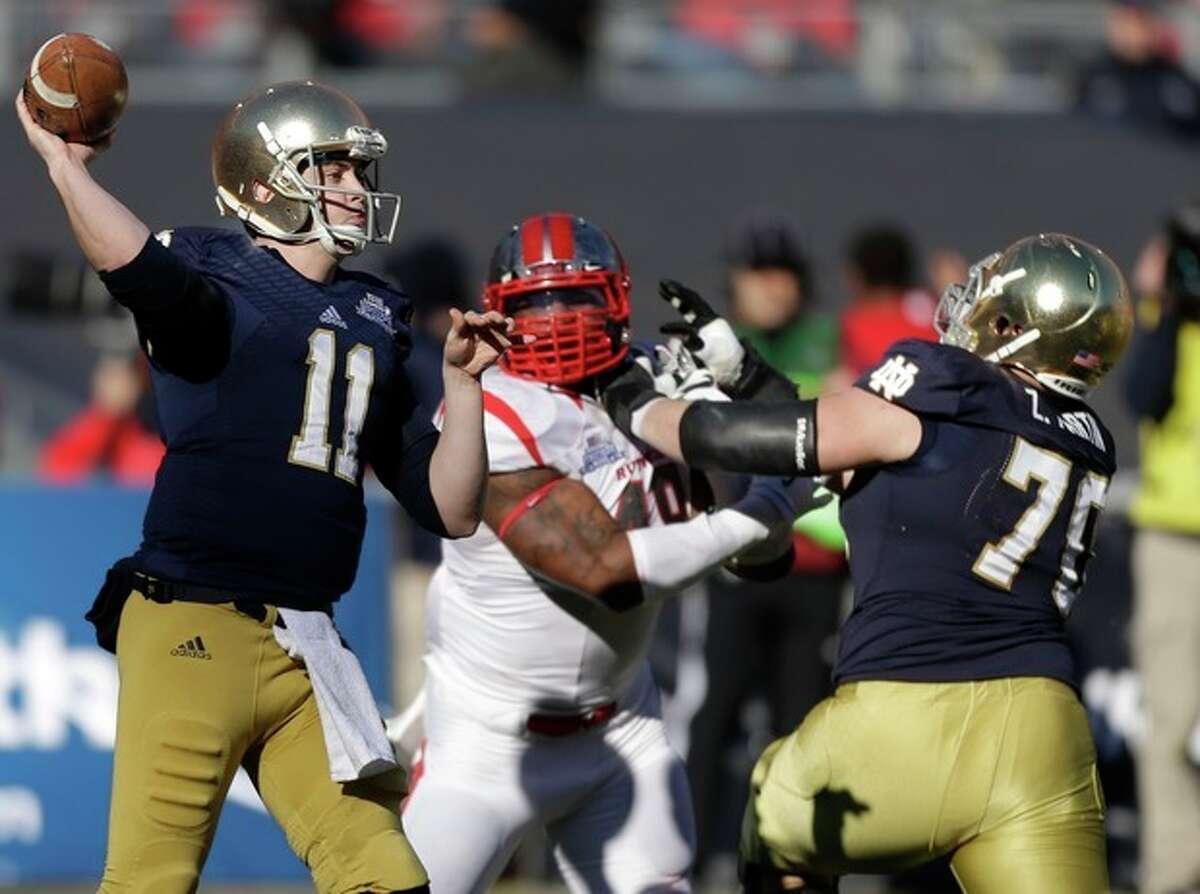Notre Dame quarterback Tommy Rees (11) throws a pass as lineman Mark Harrell (75) blocks Rutgers' Marcus Thompson (48) during the first half of the Pinstripe Bowl NCAA college football game Saturday, Dec. 28, 2013, at Yankee Stadium in New York. (AP Photo/Frank Franklin II)