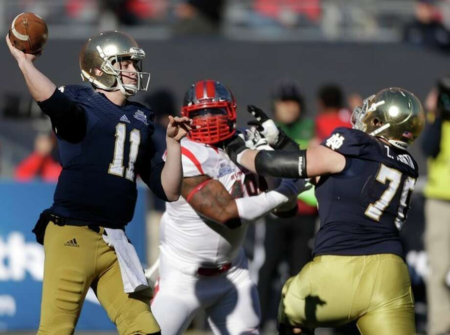 Notre Dame quarterback Tommy Rees (11) throws a pass as lineman Mark Harrell (75) blocks Rutgers' Marcus Thompson (48) during the first half of the Pinstripe Bowl NCAA college football game Saturday, Dec. 28, 2013, at Yankee Stadium in New York. (AP Photo/Frank Franklin II) / AP