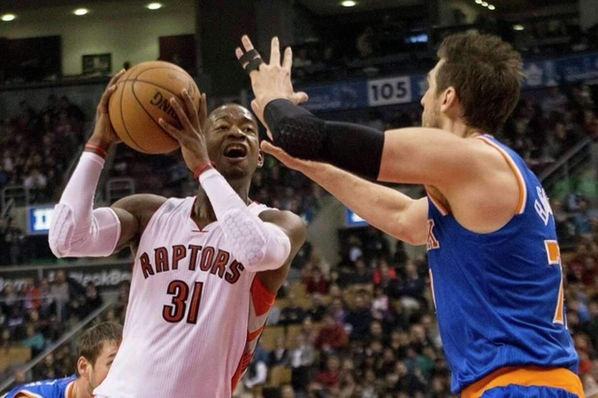Toronto Raptors' Terrence Ross, left, shoots against New York Knicks' Andrea Bargnani during first-half NBA basketball game action in Toronto, Saturday, Dec. 28, 2013. (AP Photo/The Canadian Press, Chris Young)