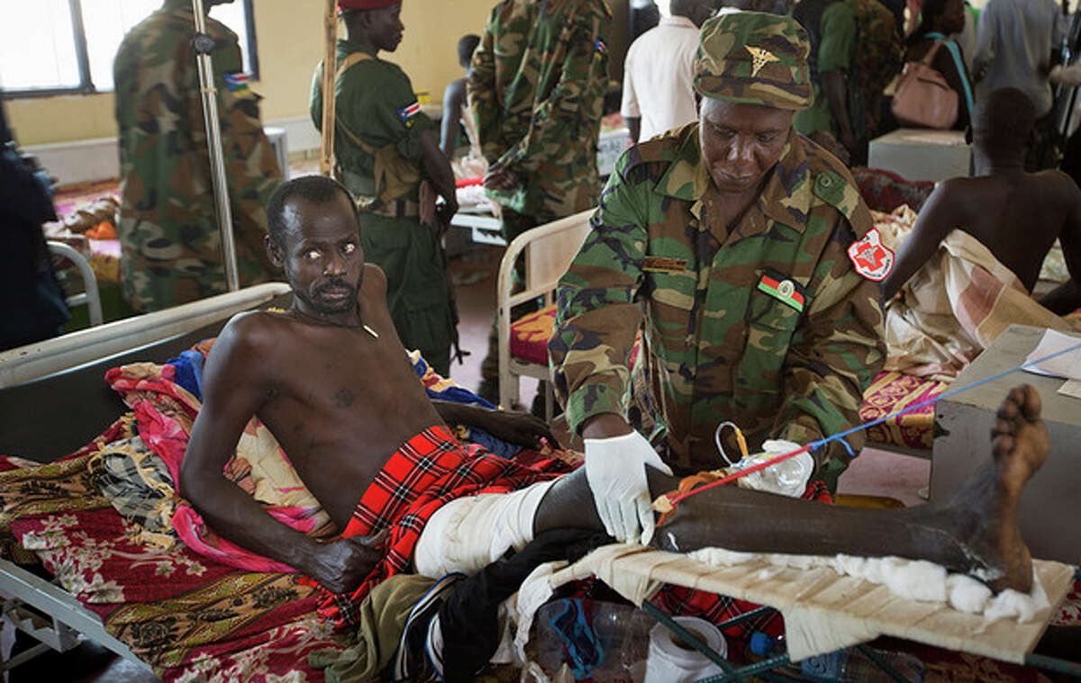 A patient is treated by a military doctor in a ward of mainly soldiers with gunshot wounds, during a visit by current Vice-President James Wani Igga, at the Juba Military Hospital in Juba, South Sudan Saturday, Dec. 28, 2013. A spokesman for South Sudan's military says fighting continues in the oil-producing Unity state despite ongoing efforts by regional leaders to get both sides to agree to an immediate cease-fire. (AP Photo/Ben Curtis)
