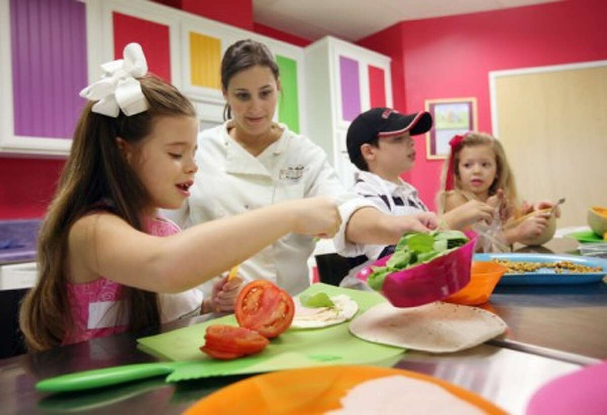 Allie Foyerlicht, second from left, of Young Chefs International, helps Kennedy Silva-Costa, 6, far left, her brother Harrison, 9, center right, and Britton, 4, make several different lunch recipes that they can learn to make for themselves, August 20, 2009, in Fresno, California. (MCT)