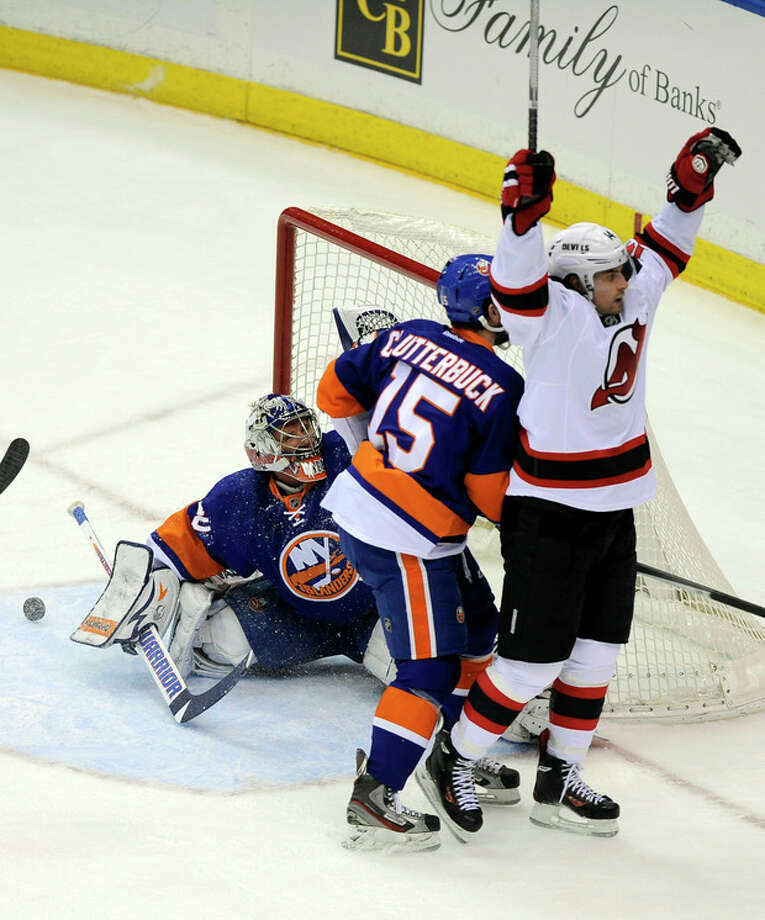 New Jersey Devils' Adam Henrique (14) celebrates after scoring a goal against New York Islanders goalie Evgeni Nabokov (20) in the first period of an NHL hockey game on Saturday, Dec. 28, 2013, in Uniondale, N.Y. (AP Photo/Kathy Kmonicek) / FR170189 AP