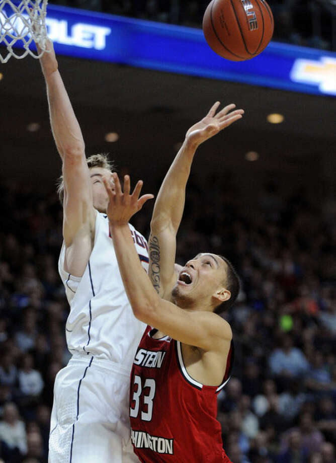 Eastern Washington's Garrett Moon (33) drives past Connecticut's Niels Giffey (5) during the first half of an NCAA college basketball game in Bridgeport, Conn., Saturday, Dec. 28, 2013. (AP Photo/Fred Beckham)