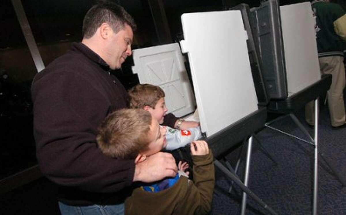 Photo/Alex von Kleydorff. Ross Manning votes as son 6yr old Max and his friend 7yr old Esteban Melendez watch during voting on election night in Wilton.