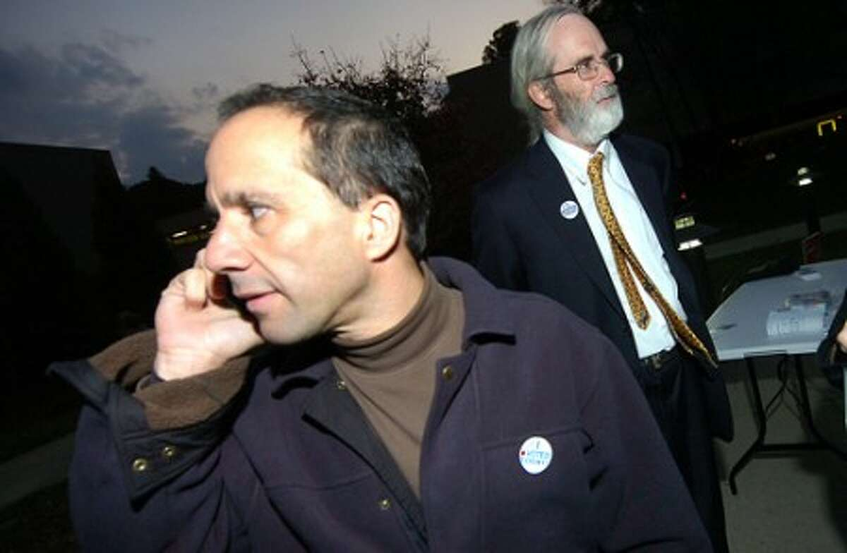 Photo/Alex von Kleydorff. Andy Pforzheimer running for Board of Finance makes some phone calls to other polls while campaigning in District 1 with Paul Burnham and Toni Lee.